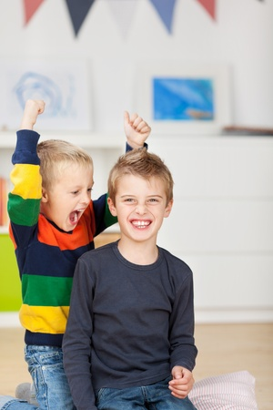naughty boy: Portrait of happy young boy with mischievous brother raising arms in house