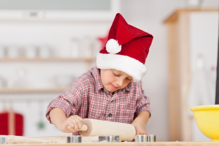 Little boy rolling dough on kitchen counter photo