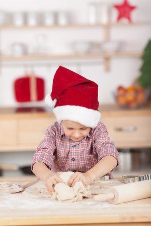 christmas cooking: Cute little boy with red hat preparing a cake for Christmas Eve Stock Photo