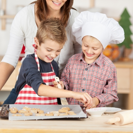 Happy brothers and mother baking cookies together at kitchen counter photo