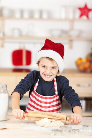Portrait of happy little boy rolling dough for cookies at kitchen counter photo