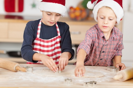 Little brothers using cutters on dough to make Christmas cookie at kitchen counter photo