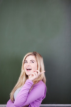 Blonde student standing in front of a blackboard has an idea photo
