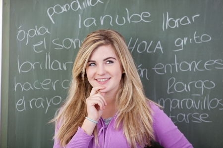 Thoughtful teenage girl with hand on chin against Spanish words written on blackboard photo