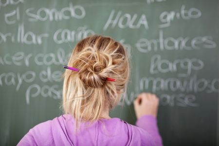 spanish girl: Female student during Spanish class in front of a blackboard