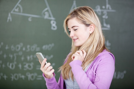 Beautiful female student reading text message on mobile phone  at classroom photo