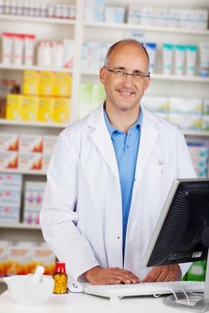 Portret van vertrouwen volwassen apotheker stond aan de balie in de apotheek Stockfoto