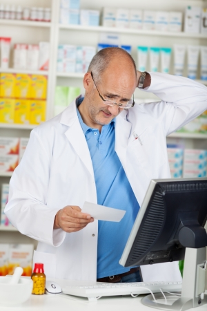 Confused mature pharmacist holding prescription paper at pharmacy counter photo