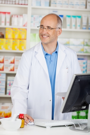 confident pharmacist behind the counter looking to the side photo