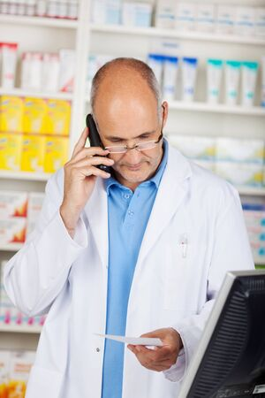 calling on phone: Mature pharmacist holding prescription paper while using cordless phone in pharmacy Stock Photo
