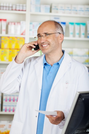 pharmacist standing in pharmacy and calling on the phone photo