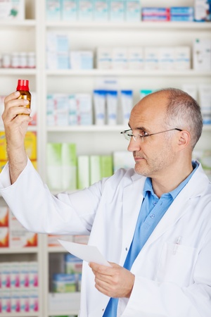 glases: mature pharmacist with glases controlling medicine, holding prescription