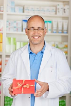 Portrait of mature pharmacist holding gift in pharmacy Stock Photo - 21246460