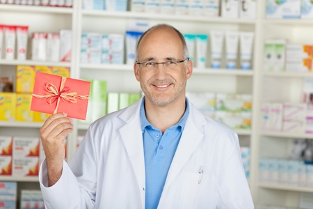 smiling pharmacist showing red coupon in pharmacy photo