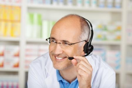 conversing: Mature male pharmacist conversing on headset in pharmacy