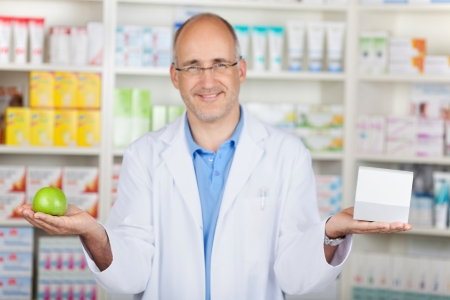 pharmacist showing apple and medicin in his hands photo