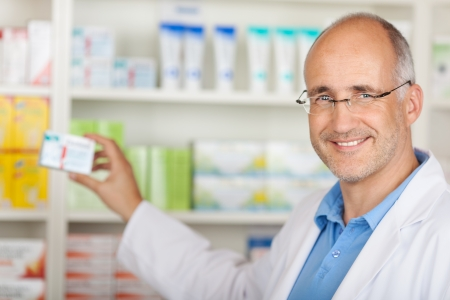 Confident mature pharmacist taking medicine from shelf at pharmacy photo