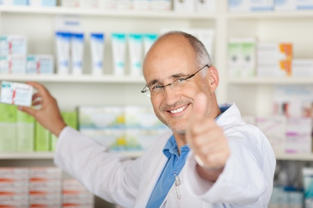 pharmacist showing thumbs up sign while taking medicine from shelf in pharmacy photo