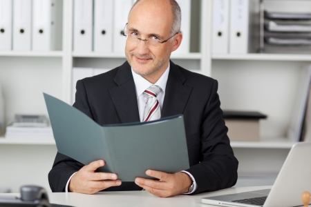 Portrait of confident mature businessman holding file at office desk Stock Photo - 21246479