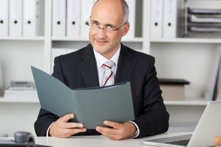 Portrait of confident mature businessman holding file at office desk Stock Photo - 21246479