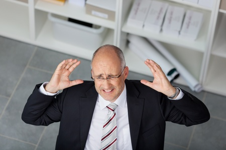 High angle view of frustrated mature businessman raising arms in office photo