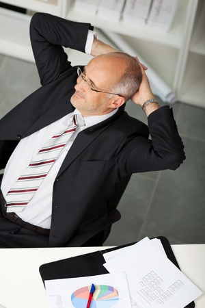 top-view of relaxed businessman leaning back in office photo
