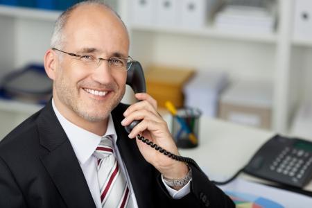 llamando: Retrato de hombre de negocios feliz con teléfono fijo en el escritorio de oficina Foto de archivo