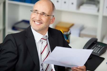 contemplative: Happy thoughtful businessman holding paper while looking away at office desk