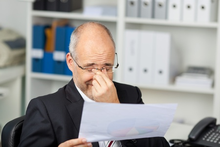 Mature businessman holding document while rubbing eyes in office photo