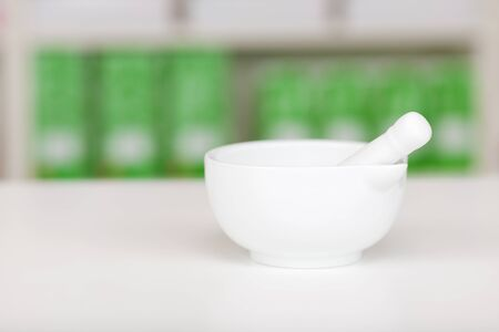 Closeup of white mortar and pestle on pharmacy counter