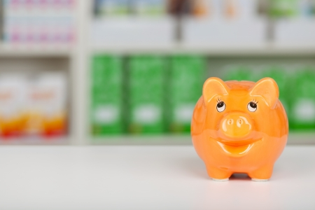 orange piggy bank standing on pharmacy counter photo