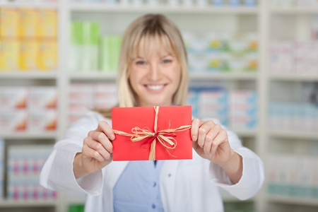 Portrait of happy female pharmacist holding wrapped gift in pharmacy photo