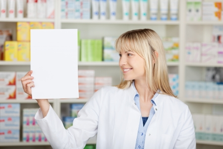 Young female pharmacist holding blank paper in pharmacy photo