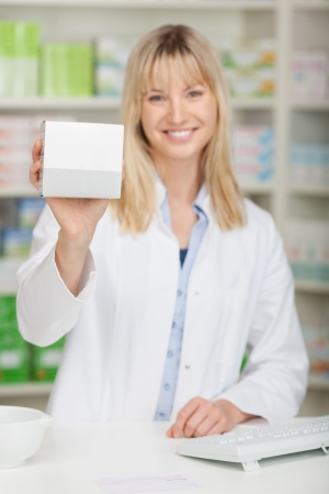 Portrait of young female pharmacist showing medicine box at pharmacy counter photo