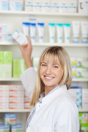 taking medicine: Portrait of happy female pharmacist taking medicine box from shelf at pharmacy Stock Photo