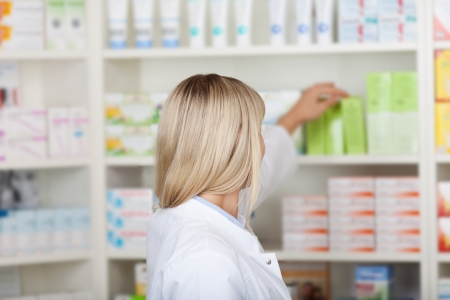 female pharmacist taking medicine from shelf in pharmacy photo