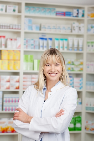 Portrait of confident female pharmacist with arms crossed standing in pharmacy photo