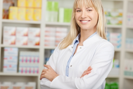 confident pharmacist standing with crossed arms in pharmacy