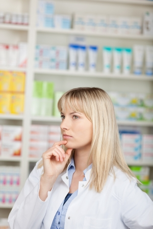 Thoughtful female pharmacist with hand on chin looking away at pharmacy Stock Photo - 21246522