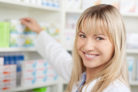 blond female pharmacist taking medicine from shelf photo
