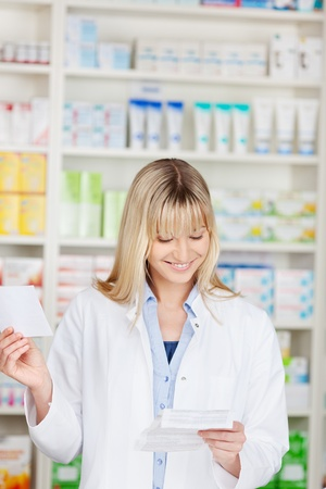 smiling female pharmacist looking at leaflet in pharmacy photo