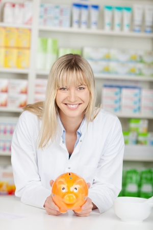 薬局カウンターにもたれながら piggybank を保持している幸せな女性薬剤師の肖像画