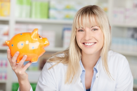 blond woman in pharmacy holding piggy bank in her hand photo