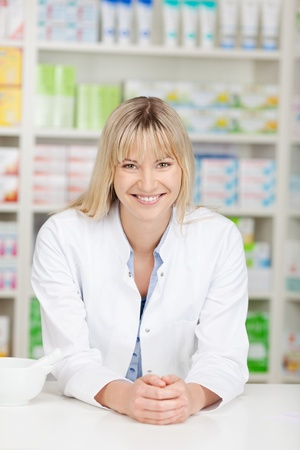 smiling blond pharmacist leaning on counter at pharmacy photo