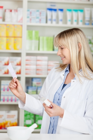 Young female pharmacist holding medicine while reading prescription paper at pharmacy counter photo