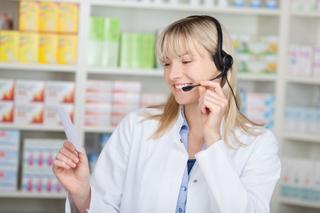 conversing: Young female pharmacist conversing on headset while holding prescription paper in pharmacy Stock Photo