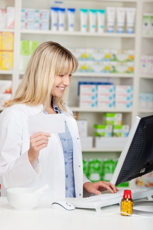 smiling female pharmacist working on computer at the counter photo