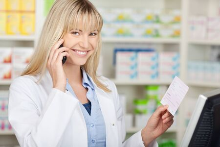 Portrait of happy female pharmacist holding prescription paper while using mobilephone in pharmacy photo