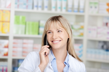 smiling confident pharmacist using telephone in pharmacy photo