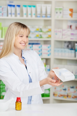 Happy female pharmacist giving paperbag of medicine at pharmacy counter photo